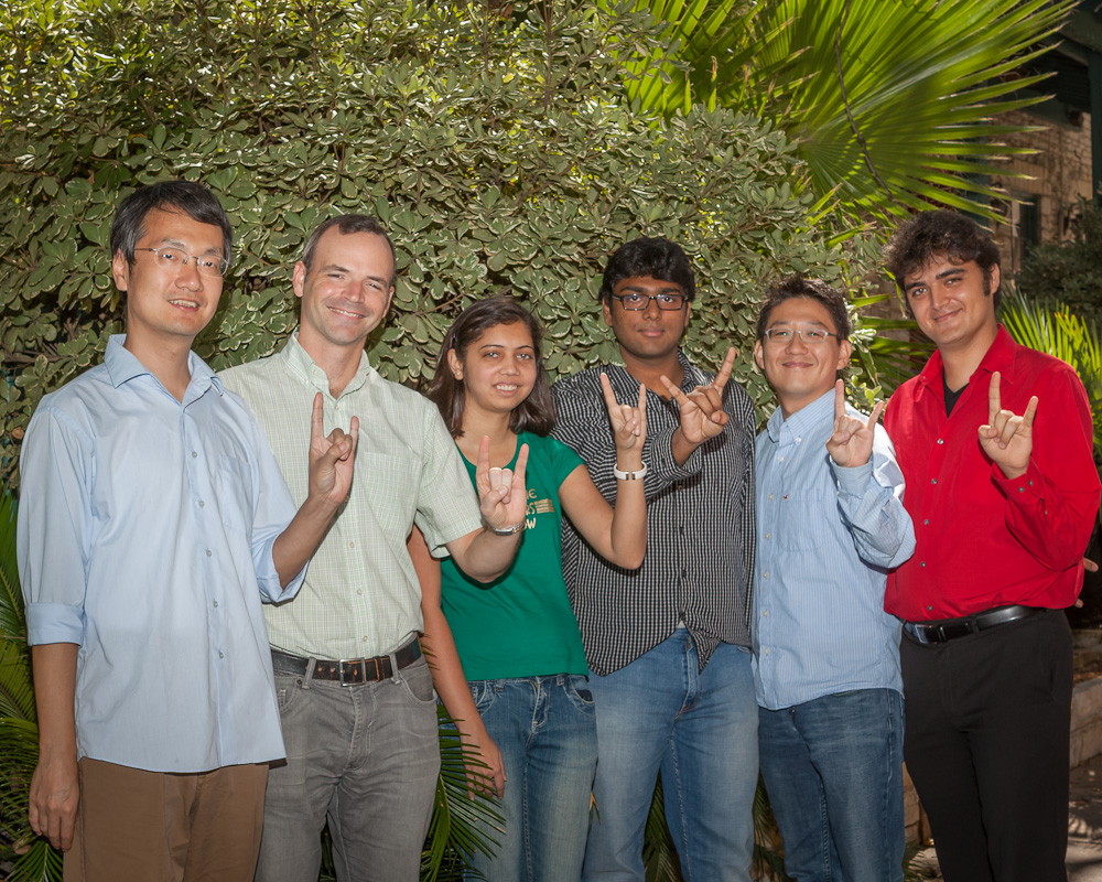 Professor Matt Lease with students of the Information Retrieval Lab making the hookem horns hand sign