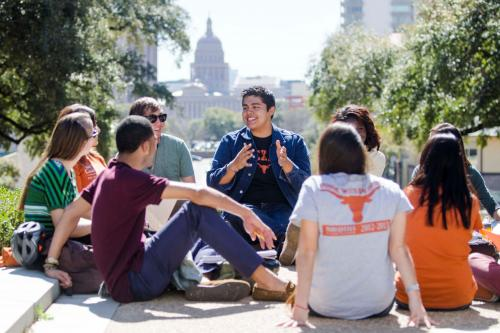 A group of undergraduate students are gather together under sunlight and talking to each other