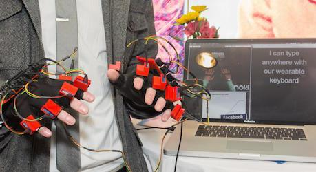 Closeup of a person using a wearable keyboard device on hands with laptop display behind