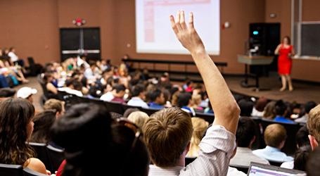 A student raises his hand to ask a question in a crowded lecture hall