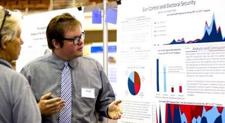 A graduate student explains his research poster