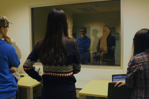 Graduate students conduct information research with in a lab with a two-way mirror