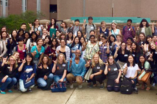 Outdoor group photo of iSchool students flashing the Hook 'em Horns hand sign