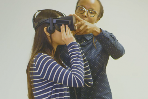 Professor Jakki Bailey assists a student wearing a VR headset in class