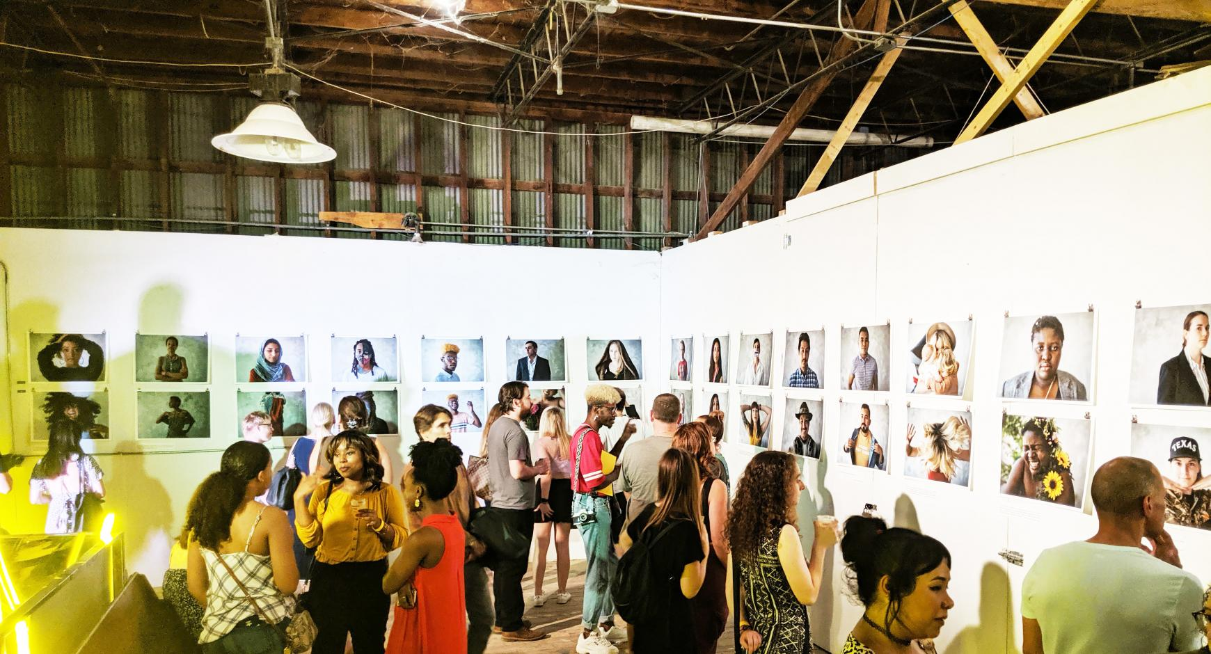 "A crowd of people attending the ""Fully Free: Identity Expression"" Art Exhibit of diverse portrait photography"