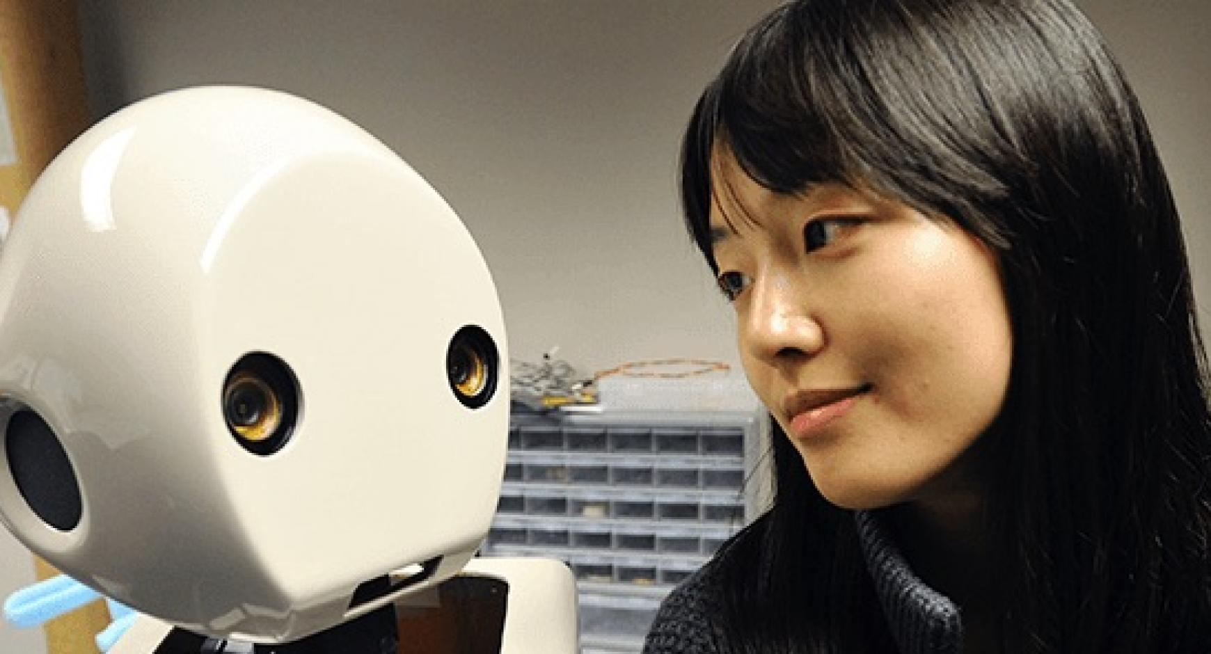 Professor Min Kyung Lee looking at the face of white robot