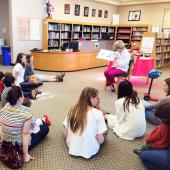 Students sit on a library floor listening to a librarian's story-time reading