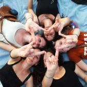 Five students lie on the ground in a circle holding up the hookem horns hand sign