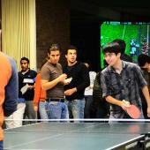 Two students playing ping pong while three others watch