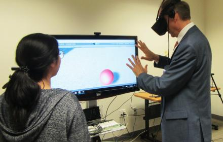 Dean Eric Meyer experiments with a graduate student's virtual reality capstone project