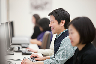 Smiling graduate students working at a long table of desktop computers
