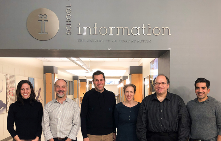 Faculty members Danna Gurari, Ed Cutrell, Roy Zimmermann, Meredith Morris, Ken Fleischmann, and Neel Joshi standing together at the interior entrance to the iSchool