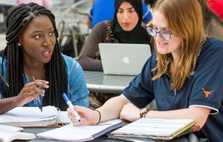 Two female students are discussing and studying