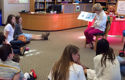 A librarian reads a picture book to children and graduate students sitting on the floor of a library