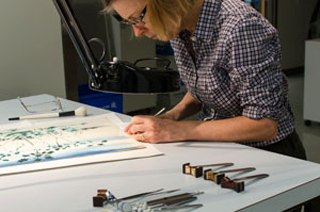 A conservator leans over a paper document on a table surrounded by conservation tools