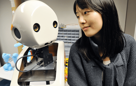 Professor Min Kyung Lee smiling at the face of white robot