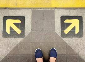 Overhead picture of two feet at the edge of a subway platform with yellow arrows pointing away in different directions