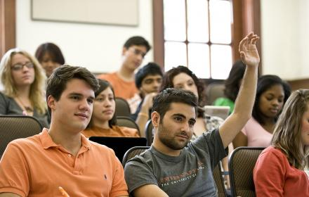 A masters student raises his hand to ask a question in a lecture hall with other students