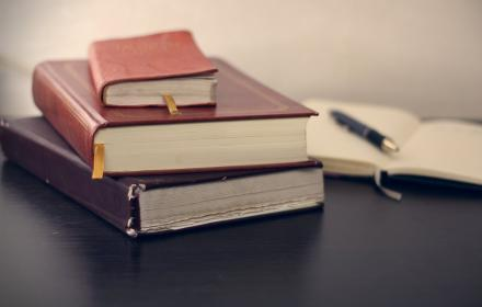 A stack of three leather-bound books next to an open notebook with pen