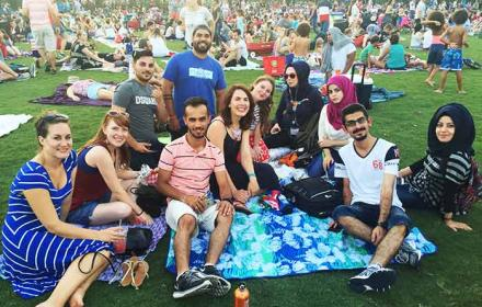 A group of international students sit on a picnic blanket